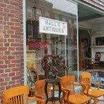 Wooden chairs line the street at this antique store.