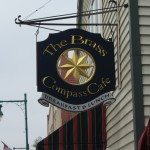 The sign for the Brass Compass Cafe