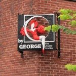 Sign on corner of brick building for By George jewlery